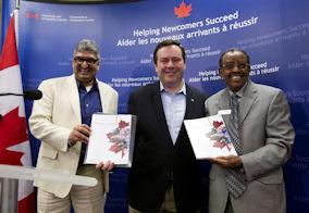 Ο Υπουργός Kenney αποκαλύπτει τον ανανεωμένο οδηγό Welcome to Canada. Αριστερά του ο κ. Nick Noorani και δεξιά ο κ. Eyob Naizghi, Εκτελεστικός Διευθυντης του MOSAIC - Βανκούβερ.